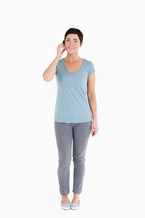 Serene woman answering the phone against a white background Stock Photo - 11227773