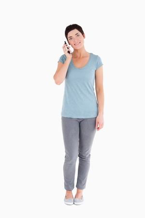 Smiling woman calling with a mobile phone against a white background Stock Photo - 11227757