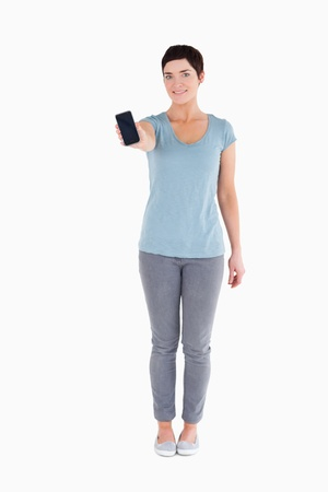 Smiling woman showing a smartphone against a white background Stock Photo - 11227566