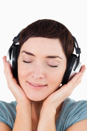 Portrait of a delighted woman listening to music music against a white background Stock Photo - 11214018