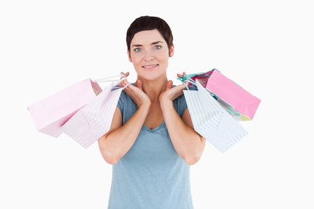 Cute woman holding shopping bags against a white background photo