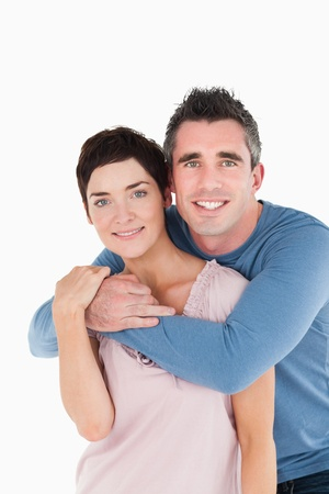 Portrait of a man embracing his wife against a white background photo