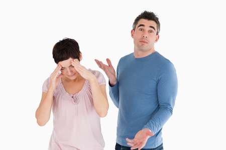 Wife crying while her husband is wondering why against a white background photo