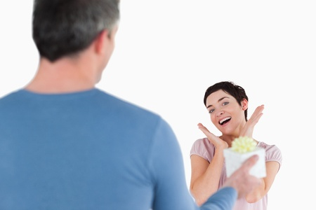 touched: Brunette woman touched by her husbands present against a white background