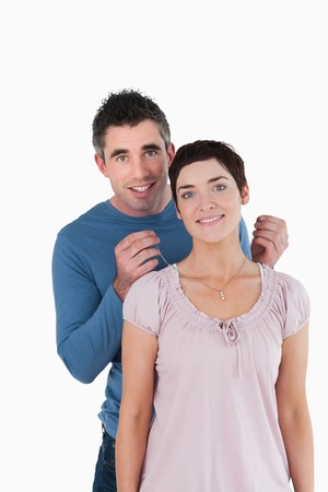 Handsome man offering a necklace to his wife against a white background photo