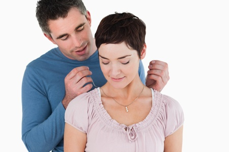 Man offering a necklace to his smiling wife against a white background Stock Photo - 11214150
