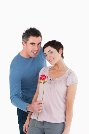 Man offering a rose to his wife against a white background photo