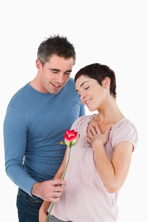 Husband offering a rose to his happy wife against a white background photo