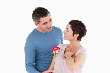 Husband offering a rose to his delighted wife against a white background photo