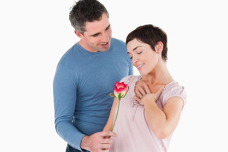 Husband offering a rose to his smiling wife against a white background photo