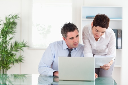 Colleagues comparing a blueprint document to an electronic one in an office Stock Photo - 11212326