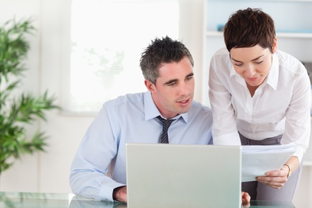 Coworkers comparing a blueprint document to an electronic one in an office Stock Photo - 11189894