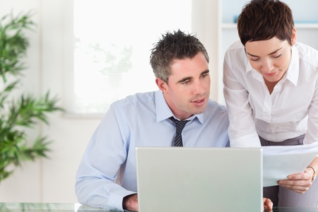 Office workers comparing a blueprint document to an electronic one in an office photo