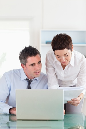 Portrait of colleagues comparing a blueprint document to an electronic one in an office Stock Photo - 11191079