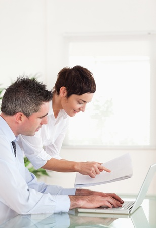 Portrait of colleagues comparing a blueprint folder to an electronic one in an office Stock Photo - 11213730