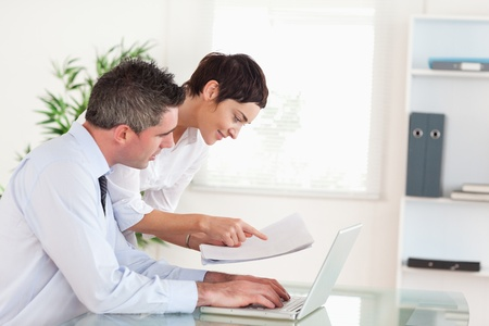 Coworkers comparing a blueprint folder to an electronic one in an office photo