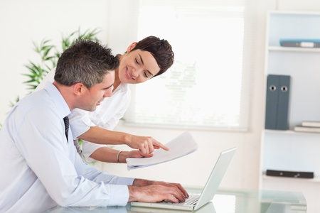 Office workers comparing a blueprint folder to an electronic one in an office photo