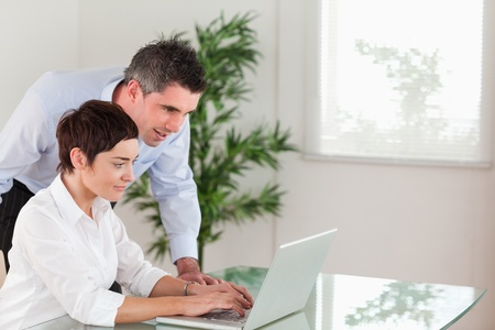 Manager and his secretary working with a laptop in an office photo