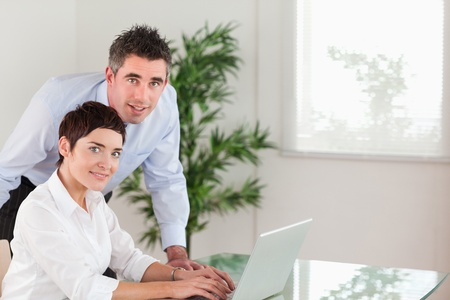 Manager and his secretary posing with a laptop in an office photo