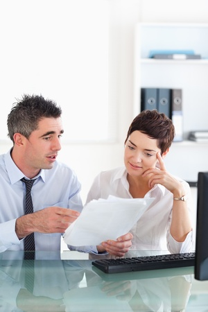 Manager pointing at something to his secretary on a blueprint document in an office Stock Photo - 11213900