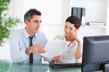 Manager and his secretary reading a blueprint document in an office Stock Photo - 11189913