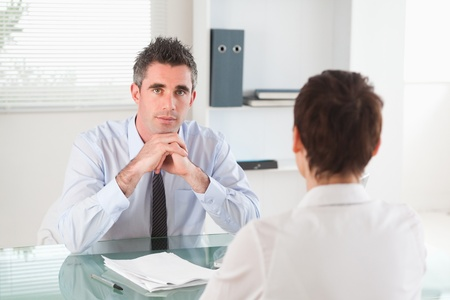 Serious manager interviewing a female applicant in his office photo