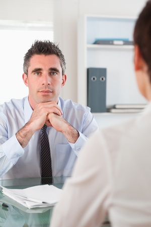 Portrait of a serious manager interviewing an applicant in his office photo