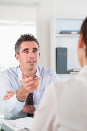 Portrait of a manager talking to a candidate in his office photo