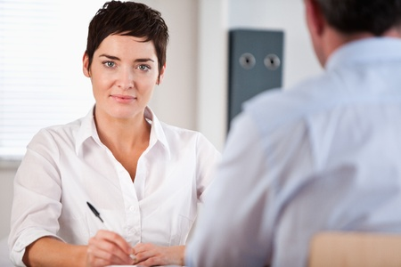 Manager interviewing a male applicant in her office photo