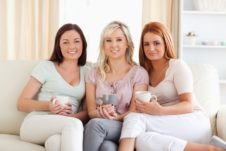 Charming women sitting on a sofa with cups in a living room photo