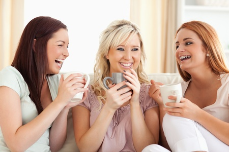 Joyful women sitting on a sofa with cups in a living room photo