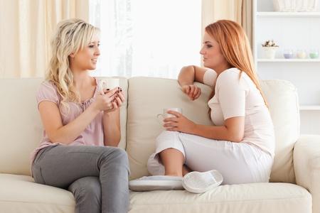 dos personas hablando: Casa de la Mujer joven sentada en un sofá con las tazas en una sala de estar Foto de archivo
