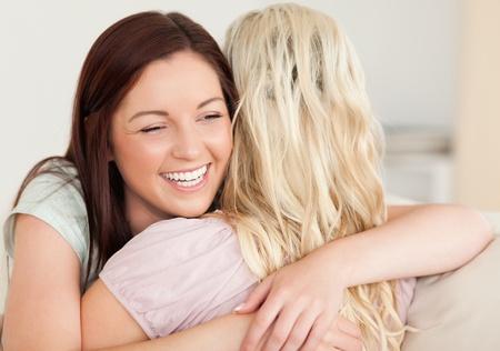 Joyful women hugging on a sofa in a living room photo