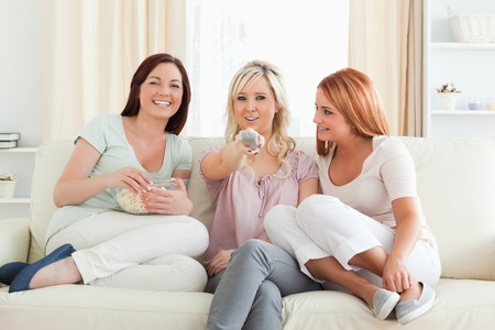 Young Women watching a movie eating popcorn in a living room photo