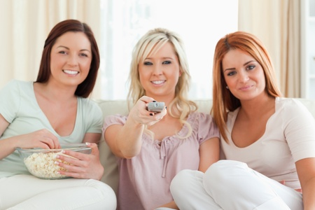 Charming Women watching a movie eating popcorn in a living room photo