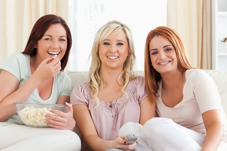 Cheerful Women watching a movie eating popcorn in a living room photo