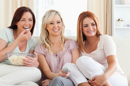 Joyful Women watching a movie eating popcorn in a living room photo