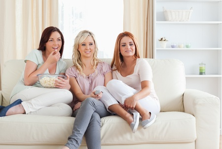 Happy Women watching a movie eating popcorn in a living room photo