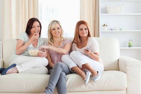 Cheering Women watching a movie eating popcorn in living room photo