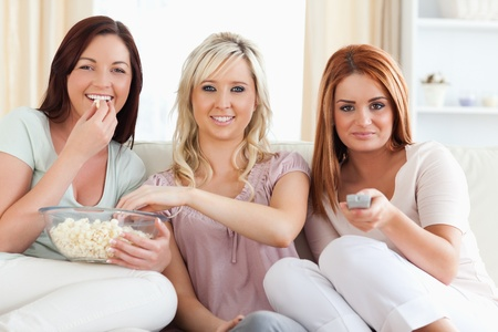 Laughing young Women watching a movie eating popcorn in a living room photo