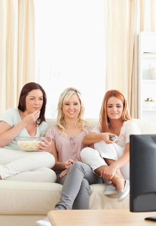 Young women lounging on a sofa watching a movie in a living room photo
