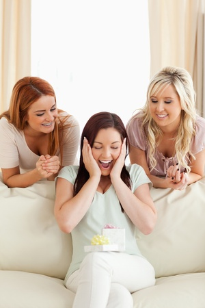 Smiling women giving their friend a present in a living room Stock Photo - 11189911