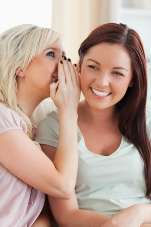 Smiling young woman telling her friend a secret in a living room photo