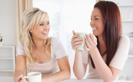 Laughing Women sitting at a table with cups in a kitchen Stock Photo - 11213241