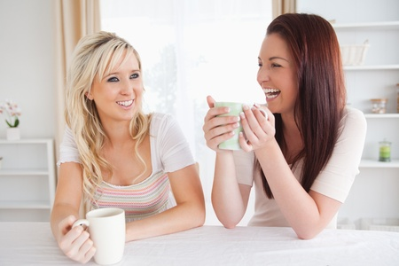 Cheerful Women sitting at a table with cups in a kitchen photo