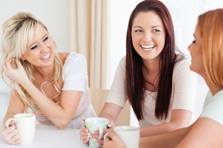 women talking: Joyful young Women sitting at a table with cups in a kitchen