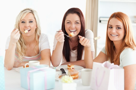 Gorgeous Women sitting at a table eating a cake in a kitchen photo