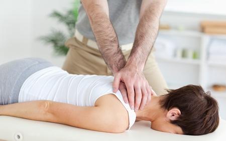 masaje deportivo: Hombre que da masajes a una mujer en una habitación Foto de archivo
