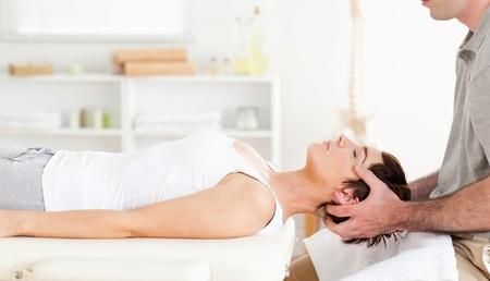 fysiotherapie: Chiropractor het oprekken van een leuke vrouw in een kamer Stockfoto
