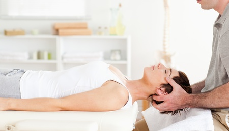 strength therapy: Chiropractor stretching a cute woman in a room Stock Photo